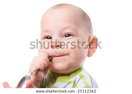 Portrait of cute boy with spoon in mouth and smile on his face - stock photo