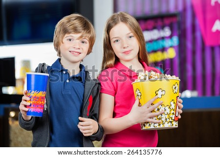 Portrait of cute brother and sister holding snacks against cinema concession stand - stock photo