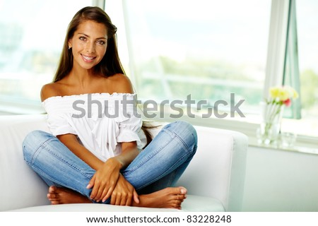 Portrait of cute brunette sitting on sofa at home - stock photo