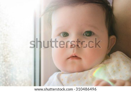 Portrait of cute caucasian little newborn baby girl sitting on mother's hands and looking at camera with beautiful brown eyes near window. Selective focus and highlights on photo make special effect. - stock photo