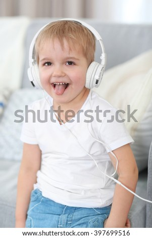 Portrait of cute cheerful boy with headphones - stock photo