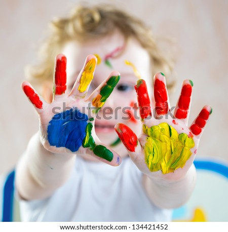 Portrait of cute cheerful girl with painted hands - stock photo