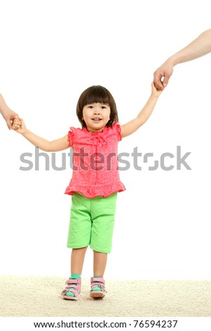 Portrait of cute child being held by her parents while walking - stock photo