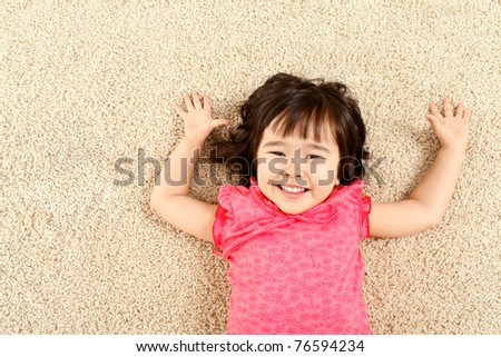 Portrait of cute child laughing while lying on rug - stock photo