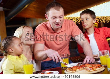 Portrait of cute children and their parents in pizzeria - stock photo