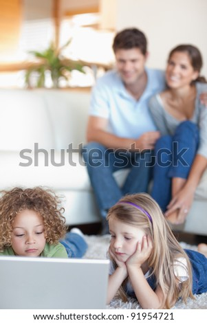 Portrait of cute children using a laptop while their parents are watching in their living room - stock photo