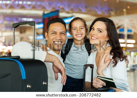 portrait of cute couple with their daughter at airport - stock photo