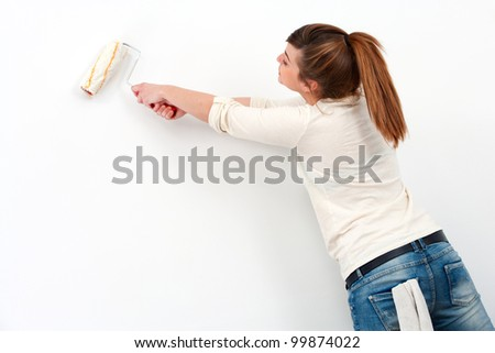 Portrait of cute female painter painting the wall.