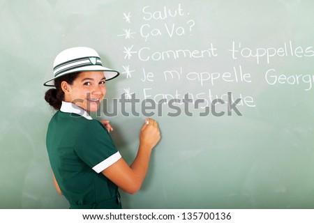 portrait of cute french schoolgirl writing on chalkboard - stock photo