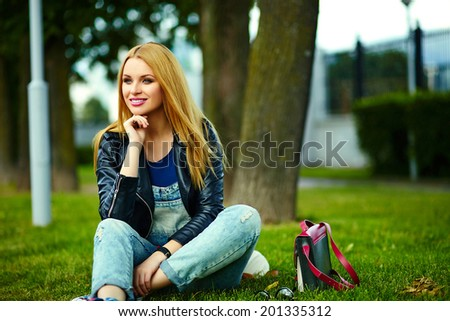 portrait of cute funny blond modern sexy urban young stylish smiling woman girl model in bright modern cloth outdoors sitting in the park in jeans with pink bag