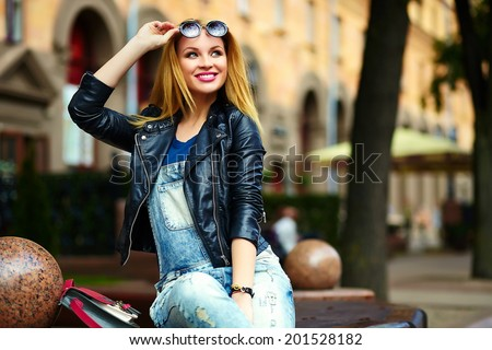 portrait of cute funny modern sexy urban young stylish smiling woman girl model in bright modern cloth outdoors sitting in the park in jeans on a bench in glasses
