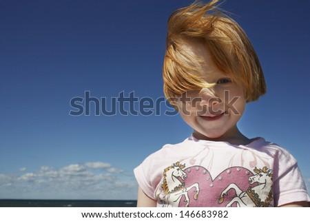 Portrait of cute ginger haired girl at beach against blue sky