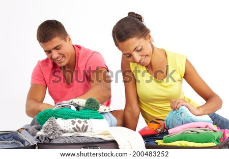 Portrait of cute girl and handsome man preparing clothes for journey  - stock photo