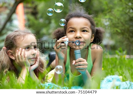 Portrait of cute girl blowing soap bubbles with her friend near by - stock photo