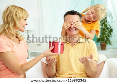 Portrait of cute girl closing male eyes by hands and happy woman holding gift for him - stock photo
