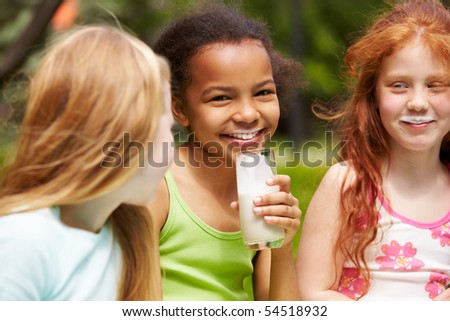 Portrait of cute girl drinking kefir outdoors with her friends near by - stock photo