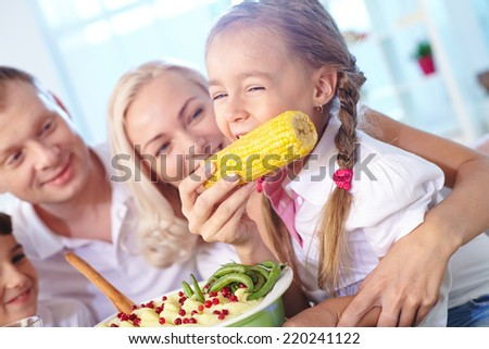 Portrait of cute girl eating corn from her mother hand and laughing - stock photo