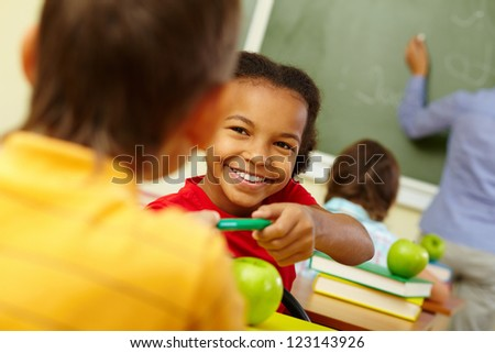 Portrait of cute girl giving crayon to classmate at lesson - stock photo
