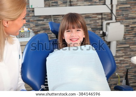 Portrait of cute girl has a dental examination. Female dentist and his smiling child patient sitting at dentist office.  - stock photo