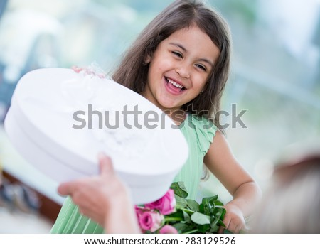 Portrait of cute girl holding gift box and flower basket at home - stock photo