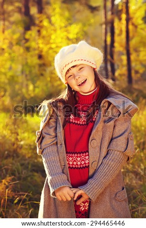 portrait of cute girl in autumn park. child outdoor