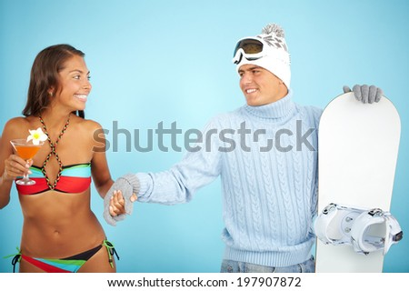 Portrait of cute girl in bikini holding cocktail and handsome man in pullover holding snowboard near by