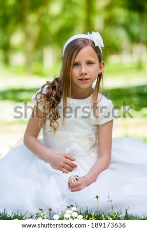 Portrait of cute girl in communion dress holding flowers outdoors. - stock photo