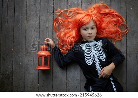 Portrait of cute girl in red wig and with lantern looking at camera - stock photo