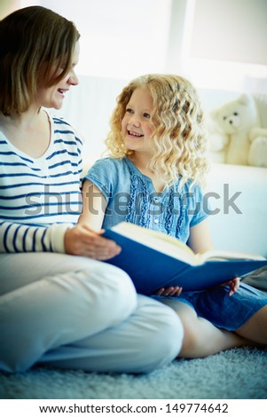 Portrait of cute girl listening to her mother reading an interesting story at home - stock photo