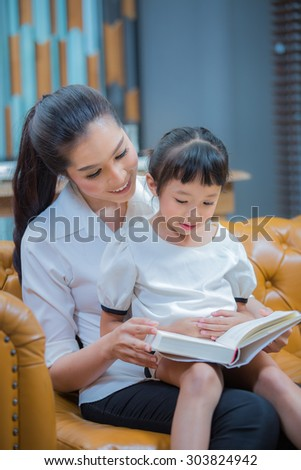 Portrait of cute girl listening to her mother telling an interesting story at home - stock photo