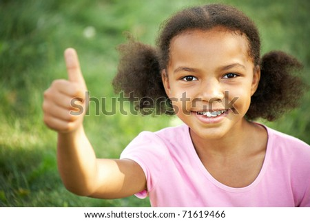 Portrait of cute girl looking at camera and showing thumb up - stock photo