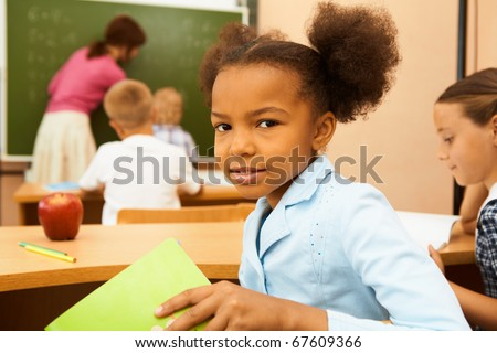 Portrait of cute girl looking at camera at workplace during lesson - stock photo