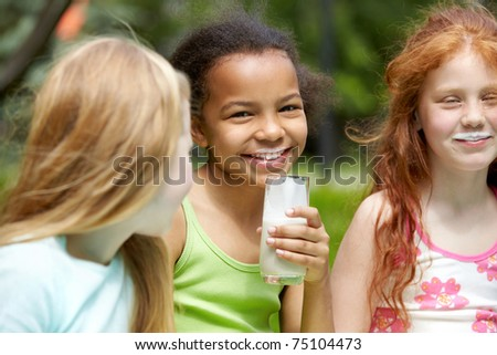 Portrait of cute girl looking at camera with her friends near by - stock photo