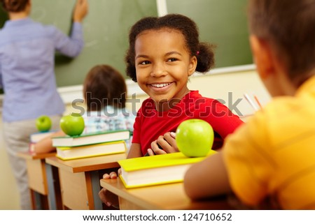 Portrait of cute girl looking at classmate at lesson - stock photo