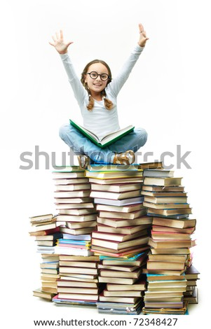 Portrait of cute girl sitting on pile of books with raised arms - stock photo