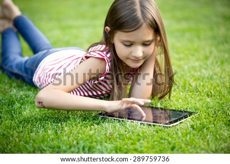 Portrait of cute girl using digital tablet at park on grass - stock photo