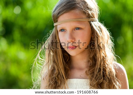 Portrait of cute girl wearing ribbon headband in green outdoors.