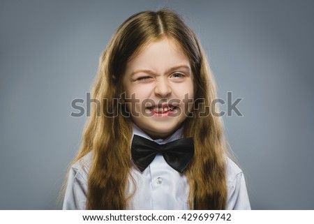 Portrait of cute girl winking over gray background. Looking at the camera. Positive human emotion facial expression body language - stock photo