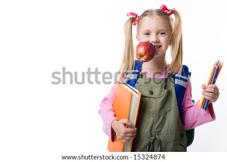 Portrait of cute girl with apple in mouth, book and pencils in hands looking at camera - stock photo