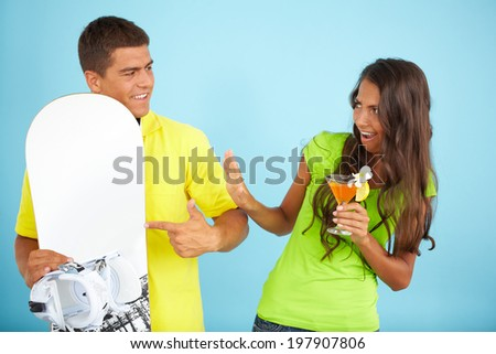 Portrait of cute girl with cocktail looking at handsome man holding skateboard near by  - stock photo