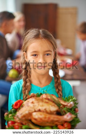 Portrait of cute girl with cooked poultry looking at camera with her family on background - stock photo