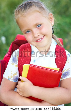 Portrait of cute girl with red backpack and books