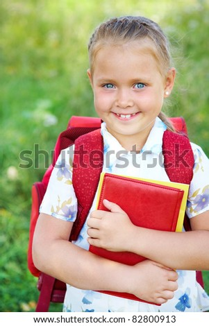 Portrait of cute girl with red backpack and books - stock photo