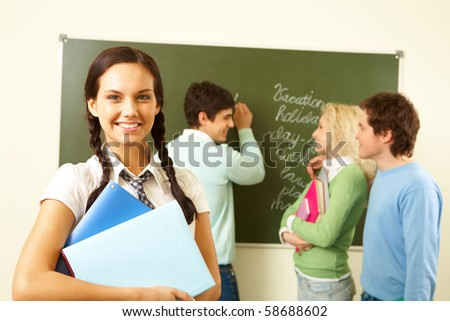 Portrait of cute girl with textbooks on background of communicating groupmates in classroom - stock photo