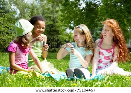 Portrait of cute girls having fun on green lawn in park - stock photo