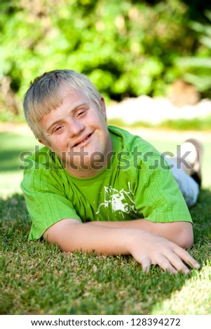 Portrait of cute handicapped boy laying on green grass. - stock photo