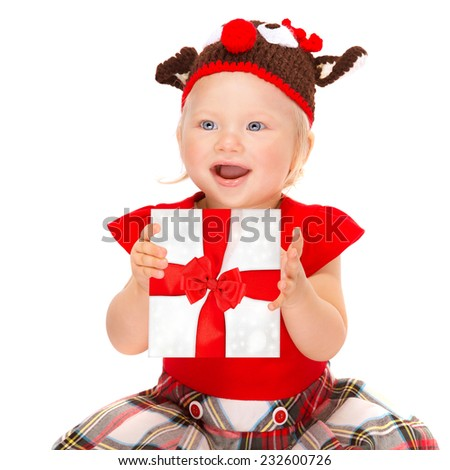 Portrait of cute happy baby girl holding in hands gift box isolated on white background, wearing festive costume, hat, Christmas time holidays concept - stock photo