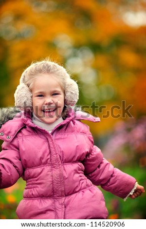 portrait of cute happy girl in warm clothes at autumn background