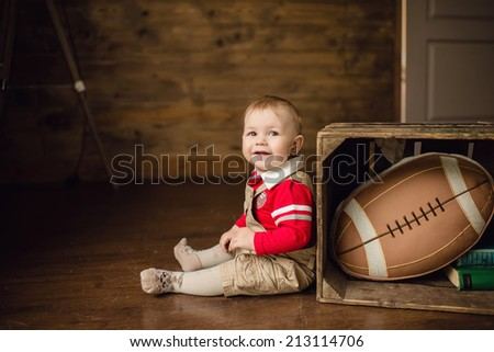 Portrait of cute happy 8 month old baby boy with american football ball - stock photo