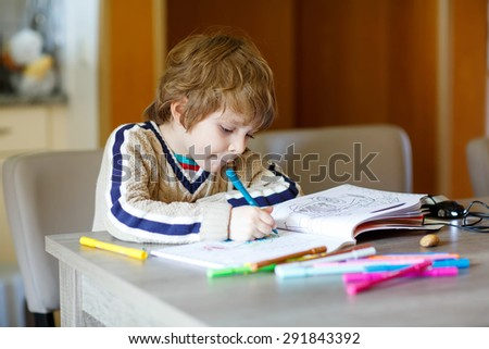 Portrait of cute happy preschool kid boy at home making homework. Little child painting with colorful pencils, indoors. - stock photo